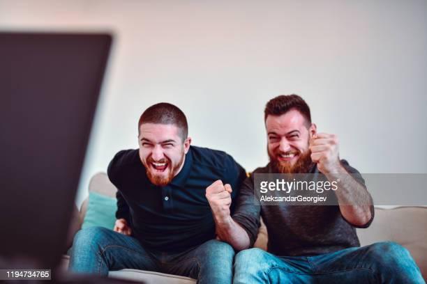 zwei männliche sportfans genießen angespanntes fußballspiel - anhänger stock-fotos und bilder