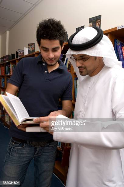 two male students browsing a book in the library - gulf countries stock pictures, royalty-free photos & images