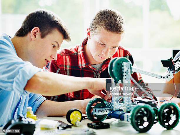 Two male students building robot together