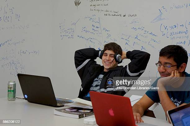 Two male students sitting at a white table with two laptops study materials and a canned energy drink whiteboard walls containing writing and...