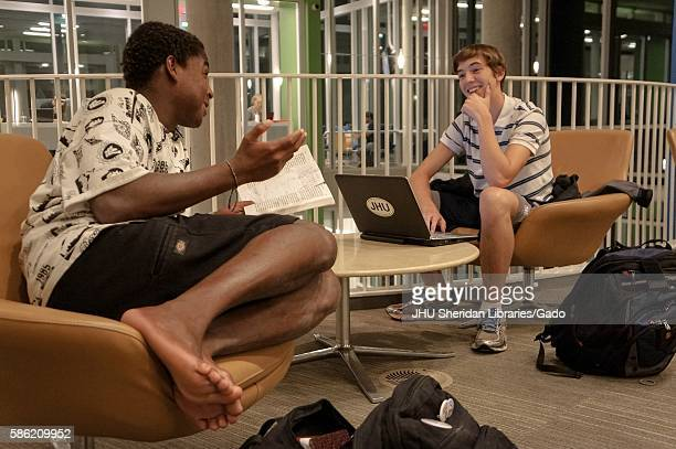 Two male students sitting on chairs of the first floor Q level of the Brody Learning Commons at Johns Hopkins University surrounded by study...