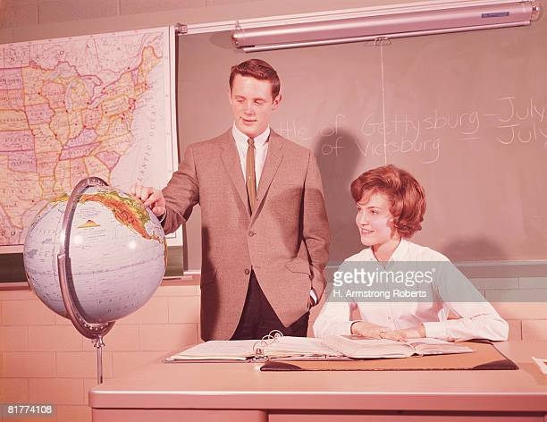 Two male students standing by world globe, girl seated at desk in classroom. (Photo by H. Armstrong Roberts/Retrofile/Getty Images)