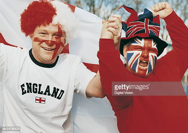 Two Male Supporters With British Flags Painted on Their Faces Holding the English Flag Cheering