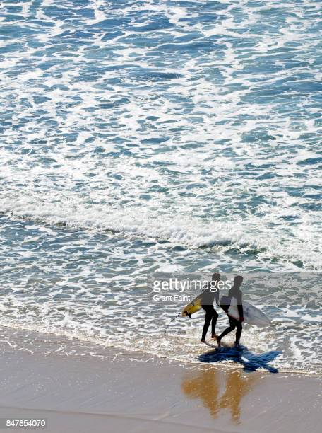 two male surfers entering ocean. - mid distance stock pictures, royalty-free photos & images