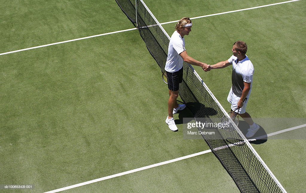 Two male tennis players shaking hands over net : Foto stock