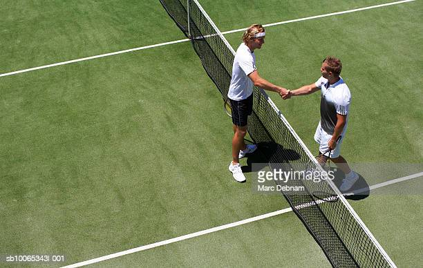 Two male tennis players shaking hands over net