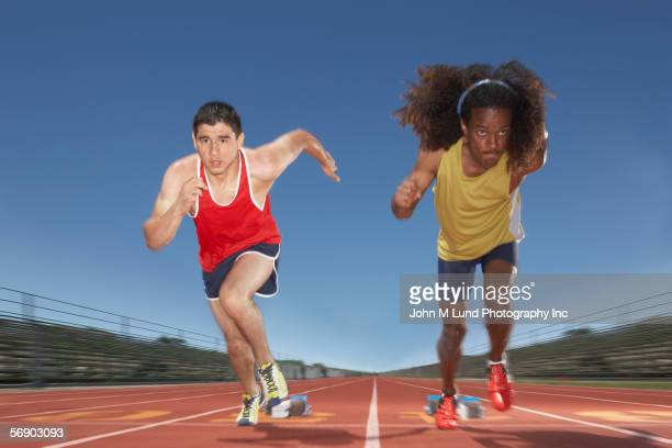 Two male track participants race