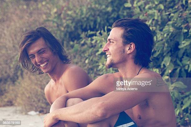 Two male travelers laughing on the beach