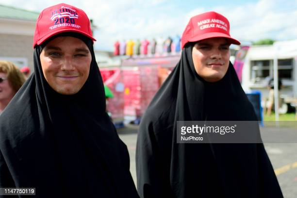Two male Trumpsupporters donning blackface and hijabs wait in line hours ahead of a campaign rally with US President Donald J Trump and his son...