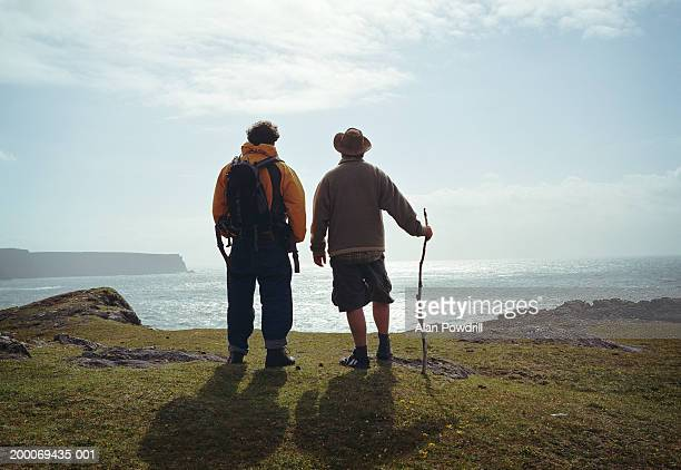 Two male walkers at edge of cliff looking out to sea, rear view