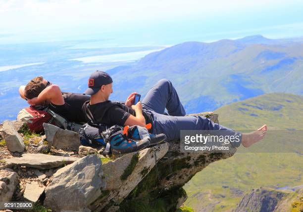 Two male walkers resting on rock overhang Mount Snowdon Gwynedd Snowdonia north Wales UK