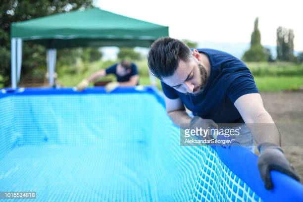 Two Male Workers Setting Up Swimming Pool In Backyard