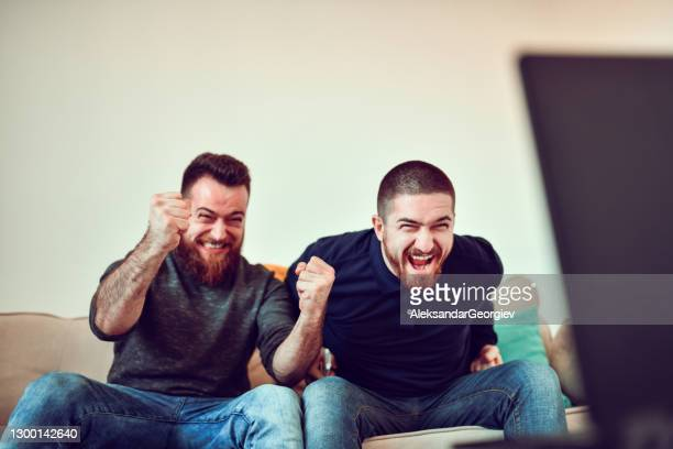 two males cheering while watching sports match on tv - fan enthusiast stock pictures, royalty-free photos & images
