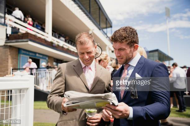 two males looking at a newspaper - newcastle races stock photos and pictures