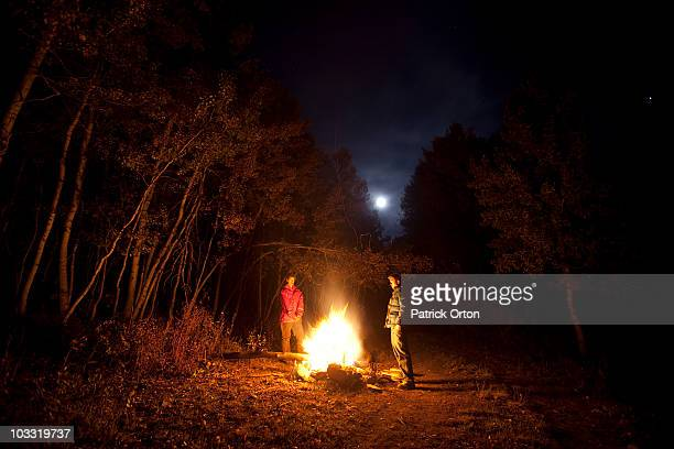 Two males standing around a fire while camping in Colorado.