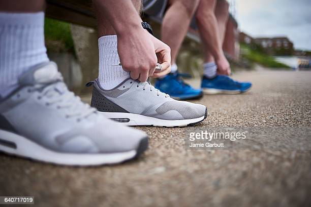 two males tying their shoes preparing for a run - low section stock pictures, royalty-free photos & images