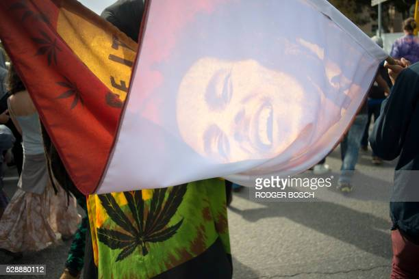 Two man carry a banner with a picture of reggae star Bob Marley and cannabis leaves joining thousands of people as they take part in a march through...