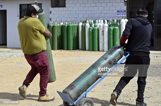Two man carry an empty oxygen tank to refill as they arrive to Valle Alto Medical Oxygen plant in Arbieto municipality, 50 km from Cochabamba, on May...