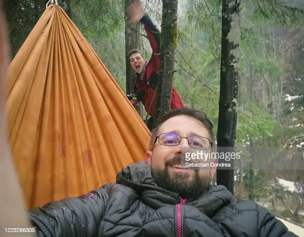 two man climbers in hammocks take selfies in the mountains, hammock hanging above the waterfall,cluj-napoca, transylvania, romania. - símbolo conceitual - fotografias e filmes do acervo