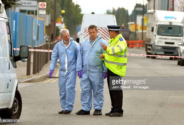 A two man forensic team prepare to search inside the Glen Cash Carry warehouse in Barking Essex where during a robbery yesterday the owner Shammi...