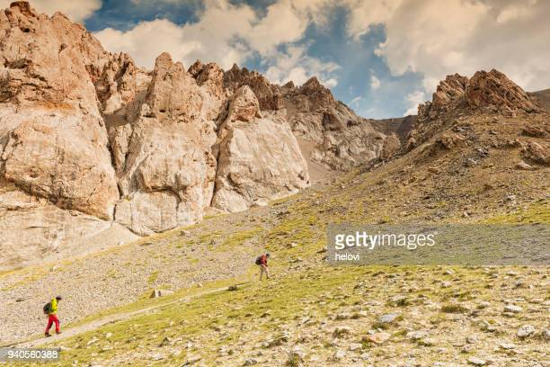 two man hiking up the steep mountain - tien shan mountains stock pictures, royalty-free photos & images