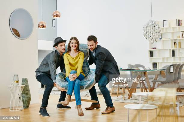 Two man in furniture shop lifting woman sitting in wrapped arm chair