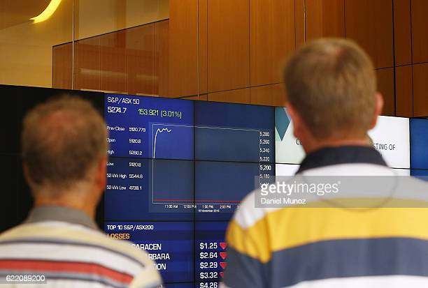 Two man look at the main board of the Australian Securities Exchange building on November 10 2016 in Sydney Australia Americans voted yesterday to...