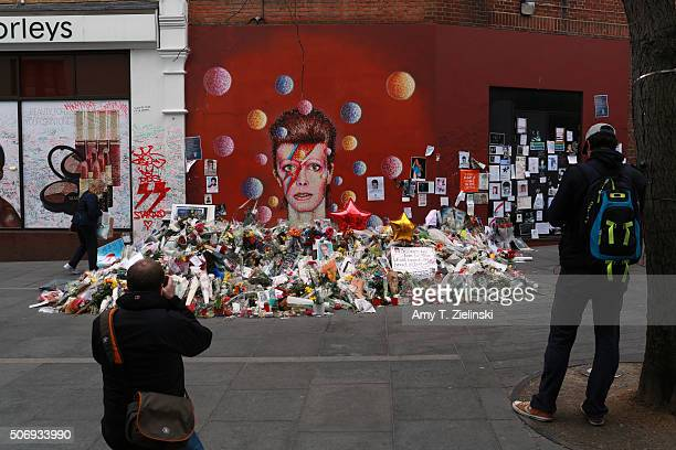 Two man photograph the flowers letters and other items left on a mound continue to grow two weeks after the death of Brixton born English singer...