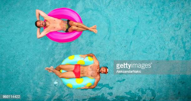 two man relaxing on inflatable rings - gay men swimwear stock pictures, royalty-free photos & images