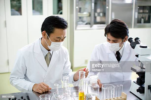 Two man scientists who work at laboratory
