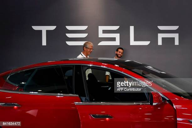 Two man stand in front of a Tesla logo behind the Tesla Model S at the electric carmaker Tesla showroom of El Corte Ingles store in Lisbon on...