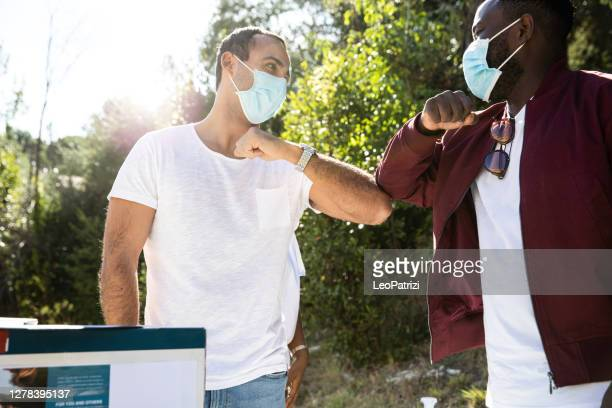 two man volunteers greetings avoiding handshakes - fundraising stock pictures, royalty-free photos & images