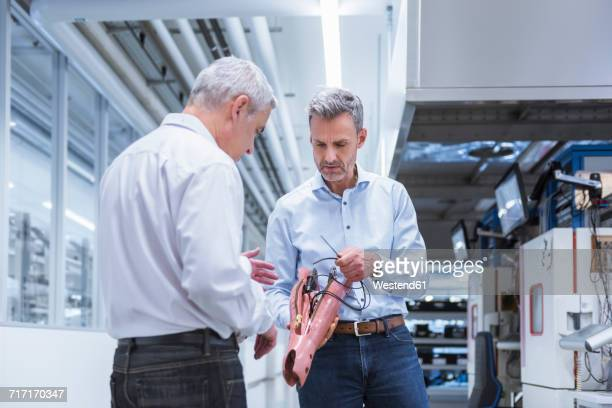 Two managers discussing construction of an prostethic leg