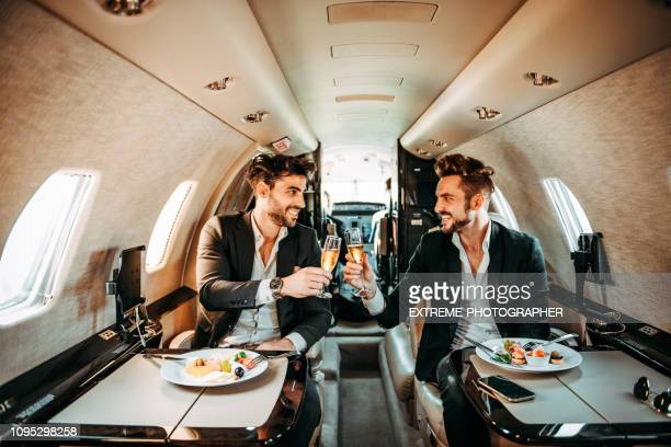 dos directores de unir sus copas en un brindis de celebración a bordo de un avión privado - casual chic fotografías e imágenes de stock