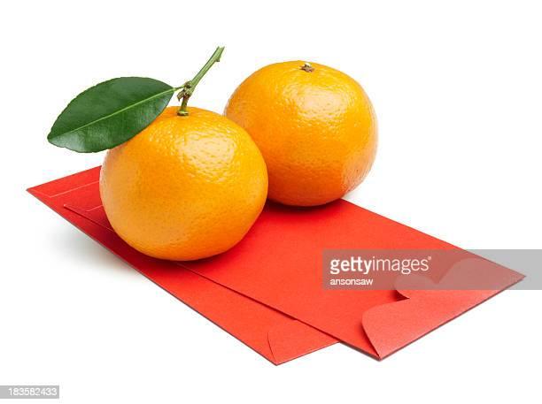 Two mandarin oranges sitting on red envelopes