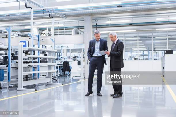 two mangagers having a meeting at the shop floor of a factory - formelle geschäftskleidung stock-fotos und bilder
