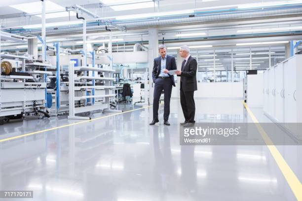 two mangagers having a meeting at the shop floor of a factory - fabrik stock-fotos und bilder