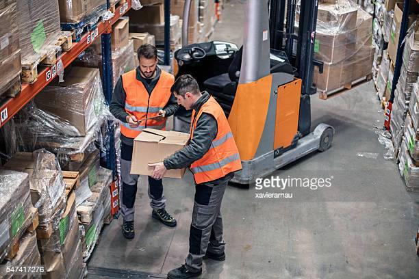 Two manual workers checking the inventory in the warehouse