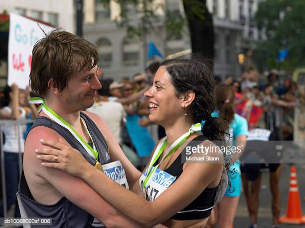two marathon runners embracing and smiling - marathon stock pictures, royalty-free photos & images