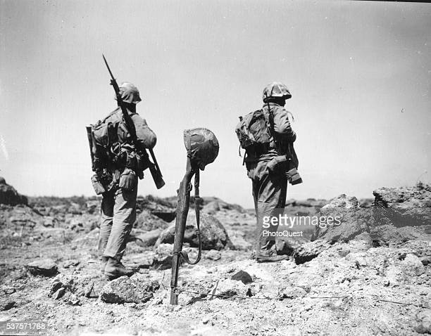 Two Marines from the First Battalion, 26th Marines, pass a temporary grave of a Marine, marked by a rifle and helmet, Iwo Jima, Japan, February 29,...