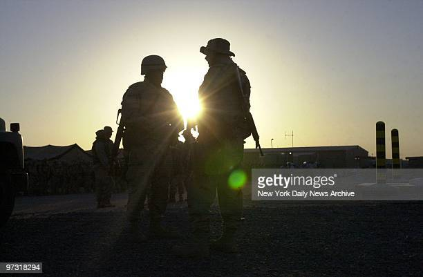 Two Marines prepare to depart with a convoy as the sun rises at Al Jaber Air Base in the Kuwaiti desert American troops and equipment are massed in...