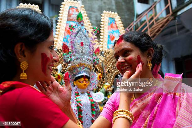 Two married women smear vermilion on one another's face as a part of the rituals on the last day of Durga puja in Kolkata, India.