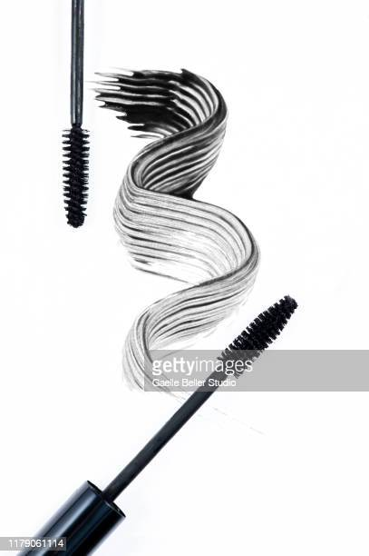 two mascara brushes next to a swirl of black mascara - mascara stock pictures, royalty-free photos & images