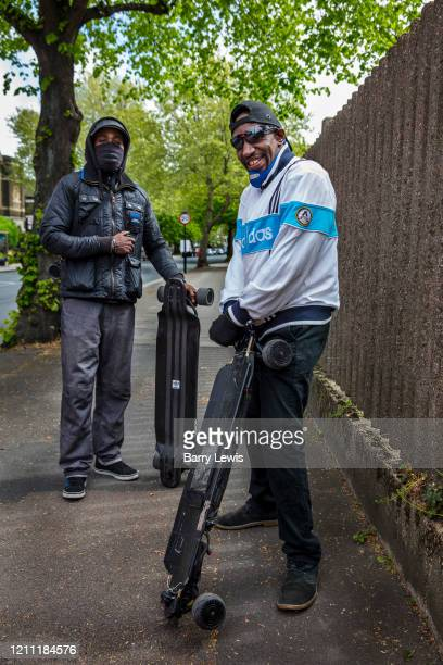 Two masked brothers staying fit in Hackney on their electric skateboards on 25th April 2020 in London United Kingdom Social distancing measures like...