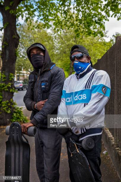 Two masked brothers staying fit in Hackney on their electric skateboards on 25th April 2020 in London, United Kingdom. Social distancing measures...