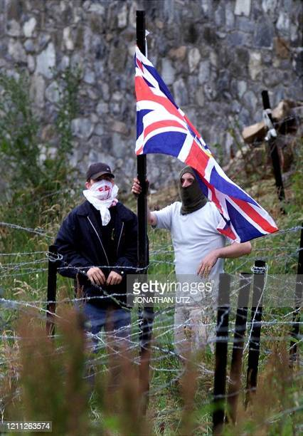 Two masked men from the loyalist side of the standoff at the Drumcree Parish Church place a British flag amongst the barbed wire in the military...