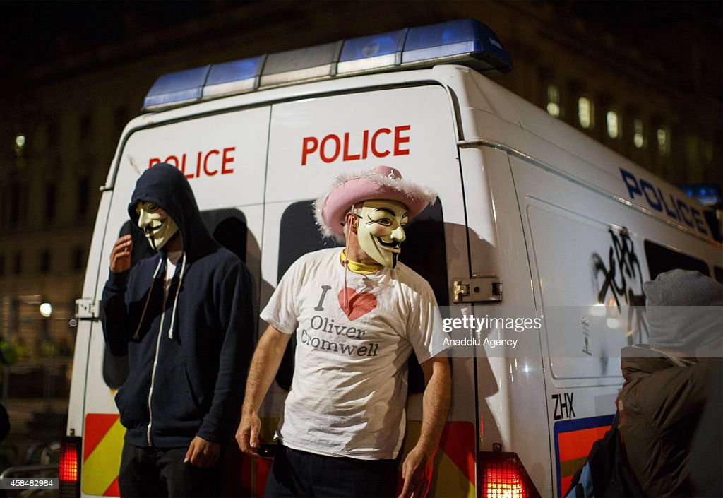 Two masked protesters hiding behind a police van which is being vandalised during the 'Million Mask March' demonstration organised by activists Anonymous in London, England on November 5, 2014. The event has become associated with protesters donning the Guy Fawkes mask made famous by graphic novel and film of 'V for Vendetta' and now used around the world as a symbol of anarchy.