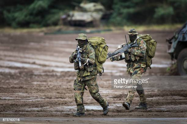 Two masked soldiers from the patrol with backpacks and guns. Shot during an exercise of the land forces on October 13, 2017 in Munster, Germany.