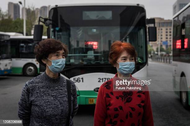 Two masked women wait for their bus at a bus terminal in Wuhan in central China's Hubei province Wednesday, March 25, 2020. The city resumed the bus...
