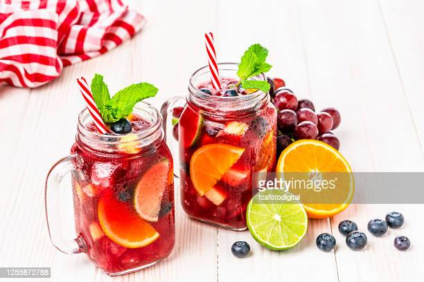 two mason jars of cold refreshing sangria with fruits on white table - sangria stock pictures, royalty-free photos & images